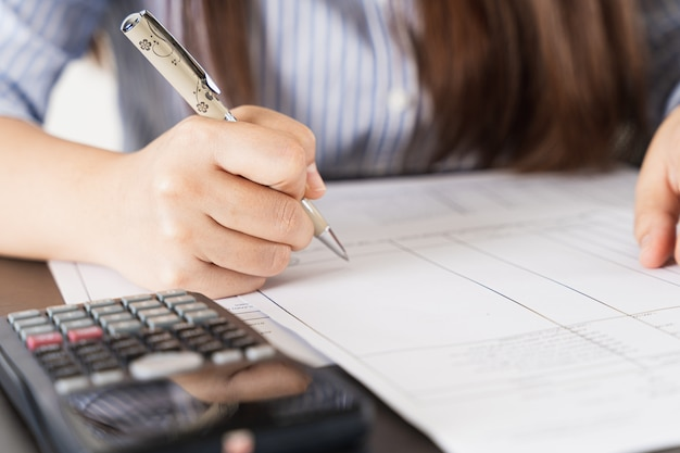 Onderneemster die aan de holdingspen van het bureaubureau werken en een calculator gebruiken