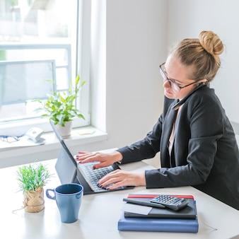 Onderneemster die aan laptop werkt die cellphone in bureau gebruikt