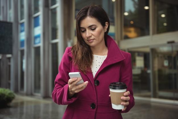 Onderneemster die beschikbare koffiekop houdt en mobiele telefoon met behulp van