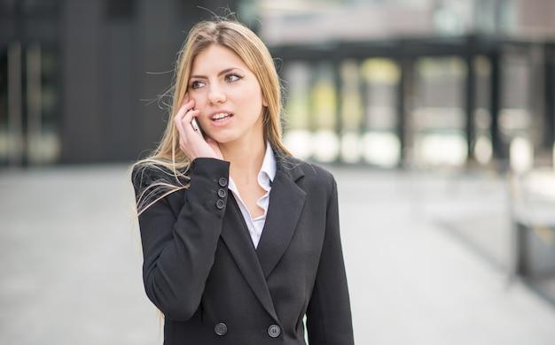 Onderneemster die bij de mobiele telefoon spreekt