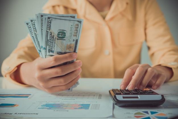 Onderneemster die calculator gebruikt en geld houdt