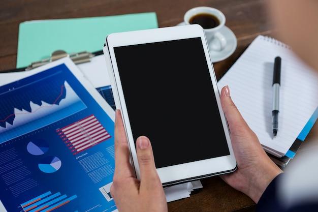 Onderneemster die digitale tablet met grafiekgrafiek gebruiken op lijst