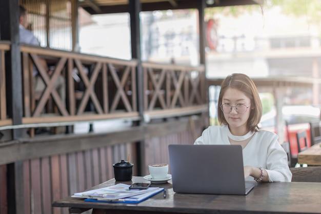 Onderneemster die door computer of laptop met behulp van die in bureaucafé werken.