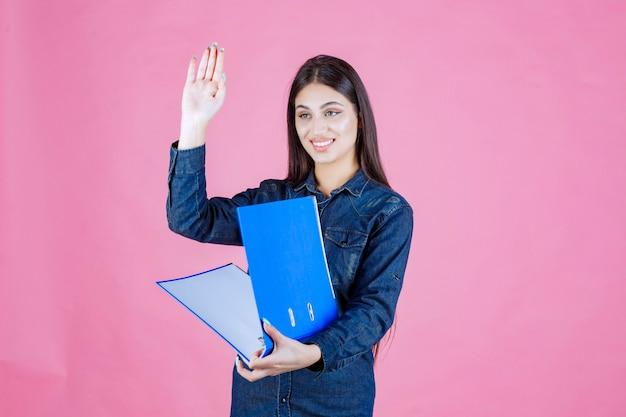 Onderneemster die een blauwe omslag houdt en iemand begroet door hand te schudden