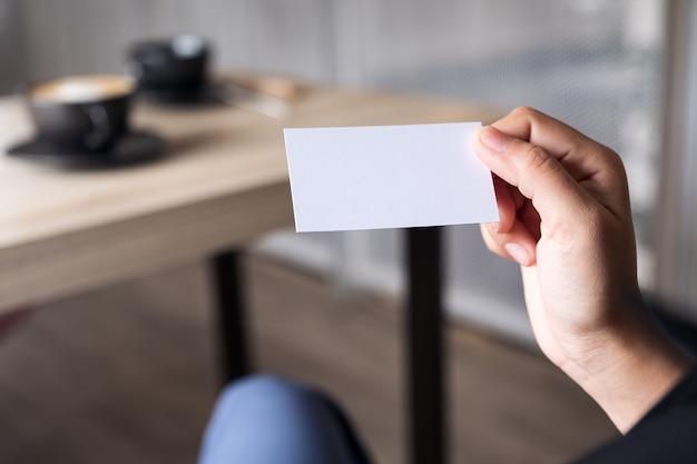 Onderneemster die een leeg adreskaartje houdt terwijl het zitten in bureau
