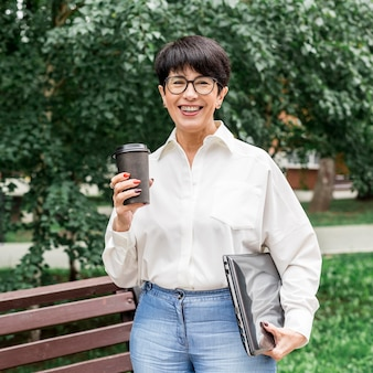 Onderneemster die en van haar koffie glimlacht geniet