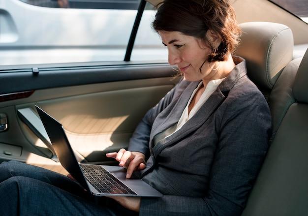 Onderneemster die gebruikend laptop auto binnen werken