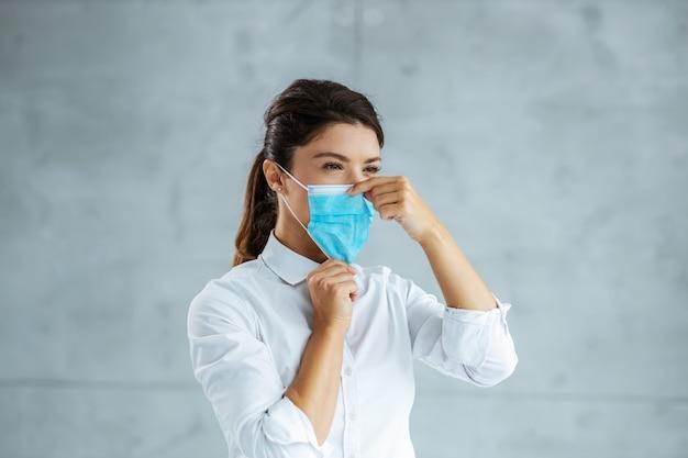 Onderneemster die gezichtsmasker correct zet. coronavirus uitbraak concept.