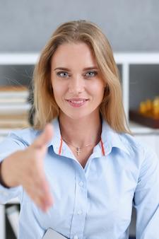 Onderneemster die hand aanbieden als hallo in bureau te schudden