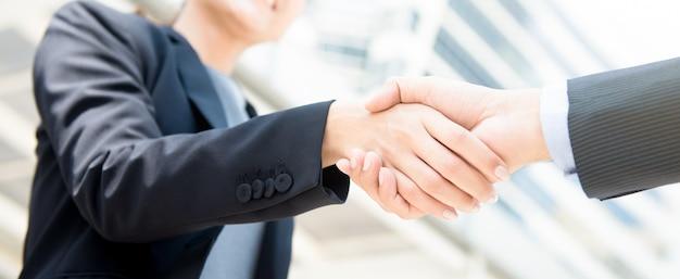 Onderneemster die handdruk met een zakenman maakt
