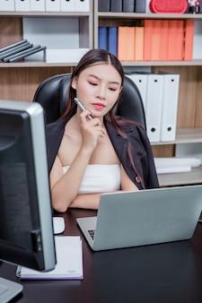 Onderneemster die in het bureau met een glimlach werkt terwijl het zitten.