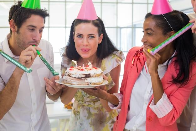 Onderneemster die kaarsen op cake uitblazen
