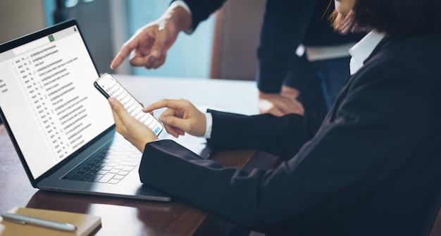Onderneemster die laptop en smartphone gebruiken die de communicatie van de e-mailschermverbinding lezen.