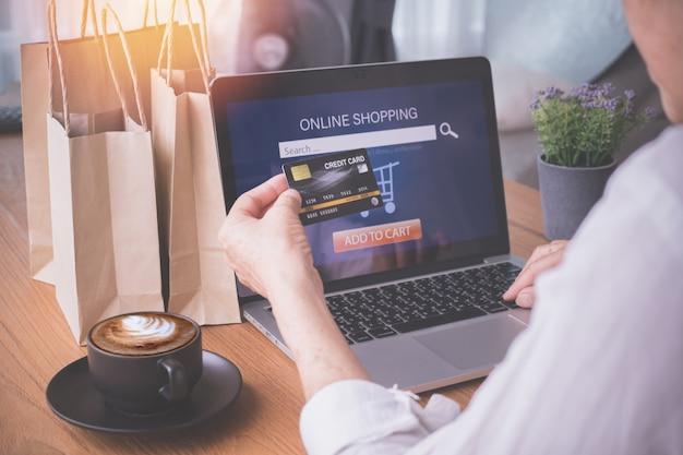 Onderneemster die laptop met behulp van die kar betaalt, concept online winkelen.
