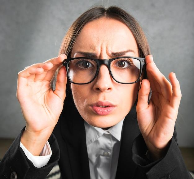 Onderneemster die merkwaardig door zwarte oogglazen tegen grijze achtergrond kijken