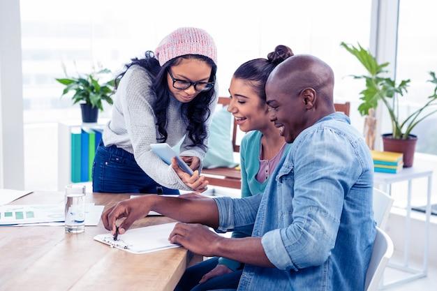 Onderneemster die met collega's over digitale tablet in creatief bureau bespreken