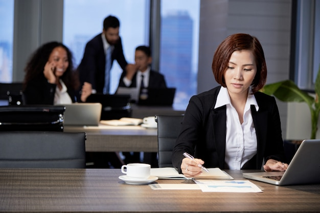 Onderneemster die met document in bureau werkt