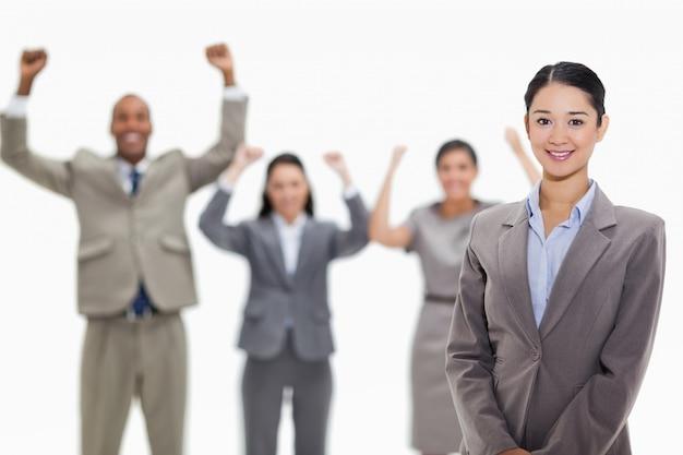 Onderneemster die met enthousiaste medewerkers glimlachen