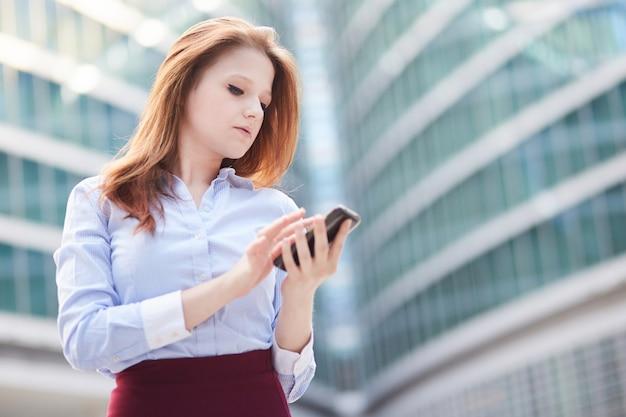 Onderneemster die met mobiele telefoon in stedelijk milieu werkt