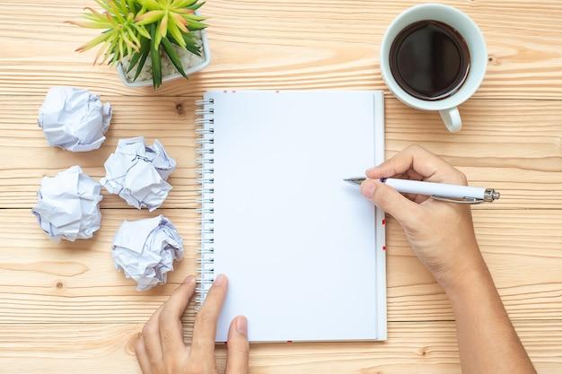 Onderneemster die met notitieboekje, crumbled document en zwarte koffiekop schrijven