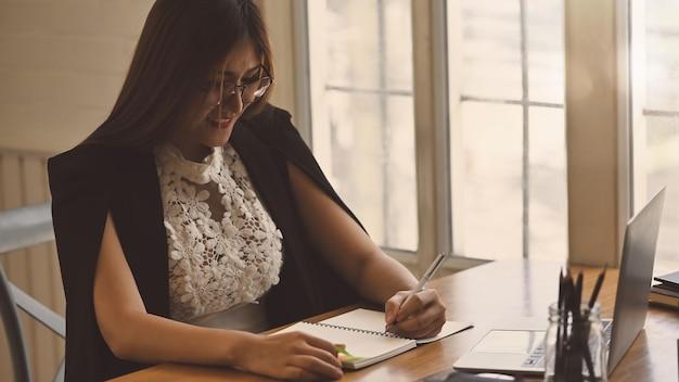 Onderneemster die met pen en notitieboekjedocument schrijft