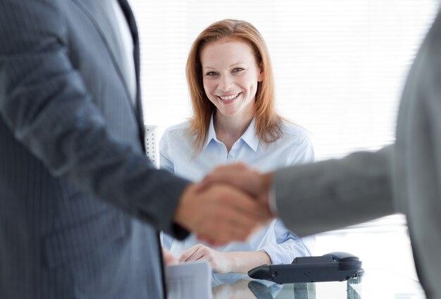 Onderneemster die met zakenlieden glimlachen die elkaar op de voorgrond begroeten