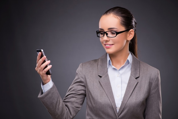 Onderneemster die mobiele telefoon in bedrijfsconcept met behulp van