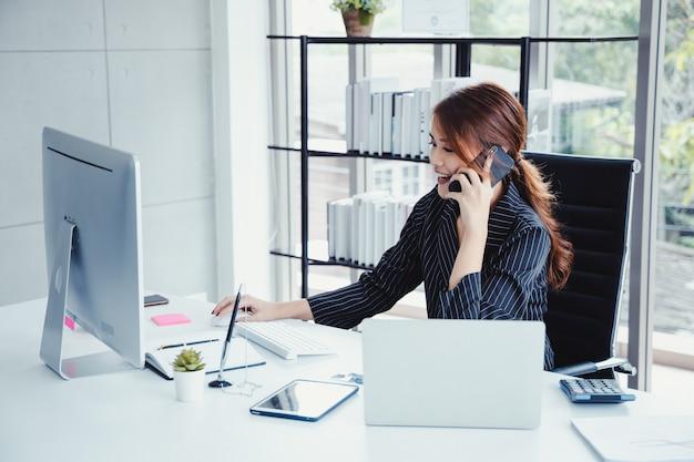 Onderneemster die mobiele telefoon met behulp van terwijl het werken in haar bureau.