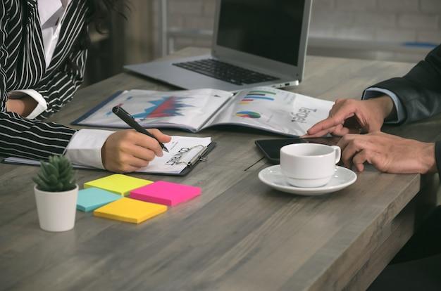 Onderneemster die officieel document leest alvorens zakelijk contract te ondertekenen terwijl zakenman op tablet op kantoor werkt. zakelijke deal concept.