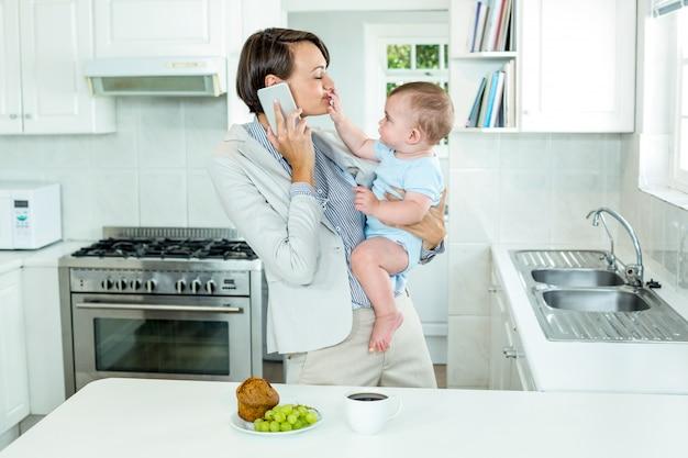 Onderneemster die op cellphone spreekt terwijl het spelen met zoon