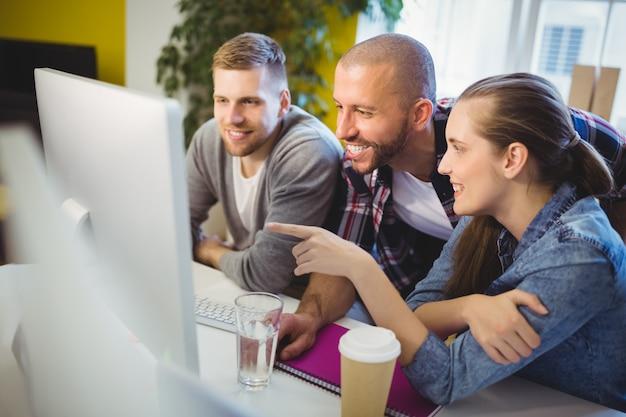Onderneemster die op computer richt terwijl het bespreken met collega's