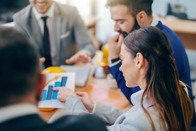 Onderneemster die op grafiek richten terwijl het zitten op vergadering in bestuurskamer. moeilijke dingen duren lang, onmogelijke dingen iets langer.