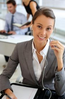 Onderneemster die op mobiele telefoon met handsfree apparaat spreekt