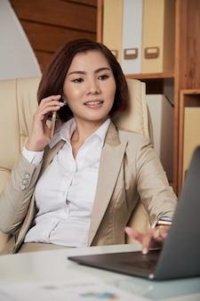 Onderneemster die op telefoon in bureau spreekt