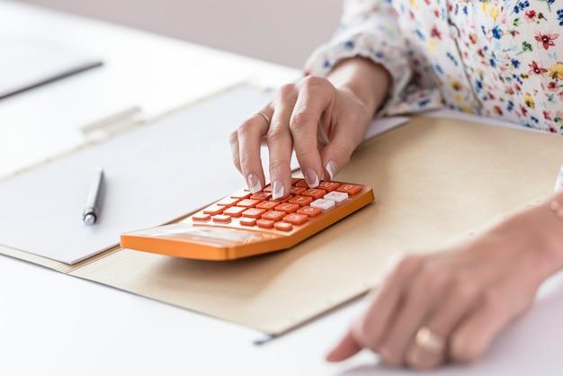 Onderneemster die oranje calculator in het bureau gebruiken