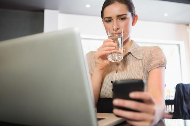 Onderneemster die telefoon in een koffie met behulp van