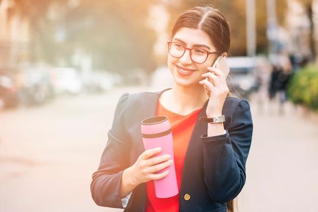 Onderneemster die telefoongesprek in openlucht maakt