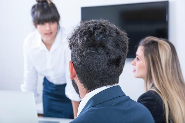 Onderneemster die zakenlui in de vergadering bekijken
