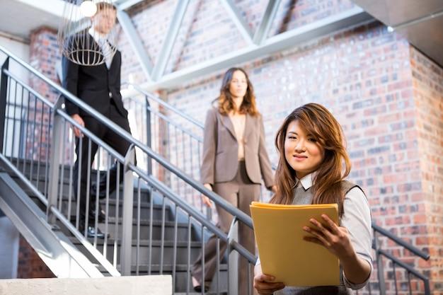 Onderneemster die zich dichtbij trap met documenten in bureau bevindt