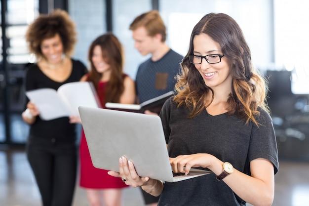 Onderneemster gebruikend laptop en glimlachend terwijl zijn collega's die zich achter hem in bureau bevinden