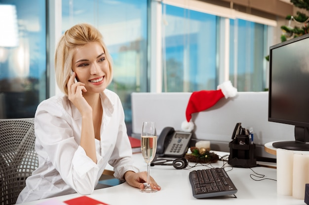 Onderneemster glimlachen die op telefoon spreken die in de dag van bureaukerstmis werken.