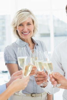 Onderneemster het roosteren met champagne in bureau