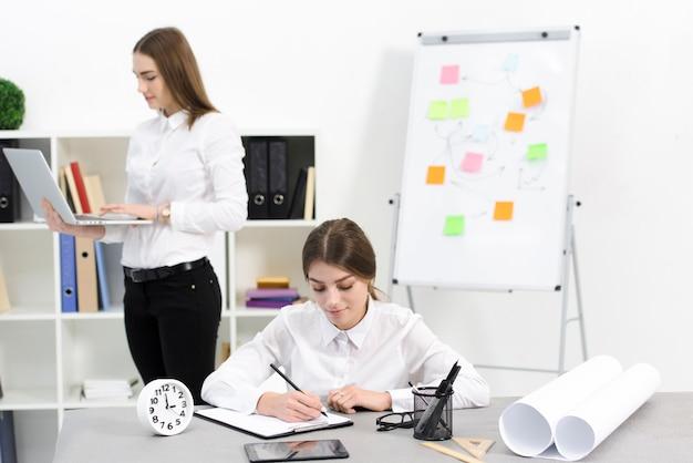 Onderneemster het schrijven nota's over klembord met haar vrouwelijke collega die digitale tablet in het bureau gebruiken