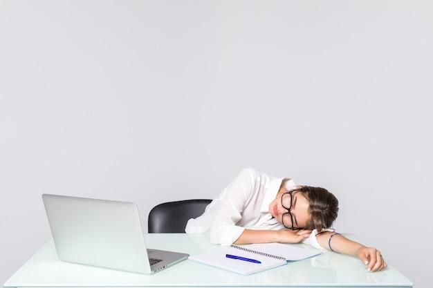 Onderneemster in slaap bij haar bureau dat op witte achtergrond wordt geïsoleerd