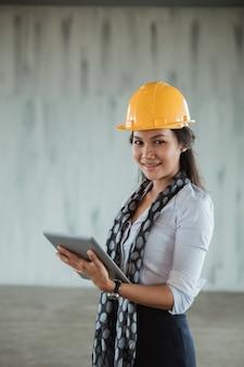 Onderneemster met bouwvakker die tabletpc in de projectplaats met behulp van