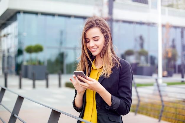 Onderneemster met een mobiele telefoon in de straat met bureaugebouwen op de achtergrond