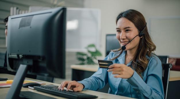 Onderneemster met hoofdtelefoon die computer en creditcard met behulp van Premium Foto