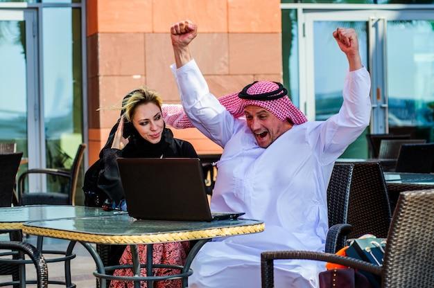 Onderneemster of verkoopster die met een arabische mens werken die producten in een tablet in een koffiewinkel tonen