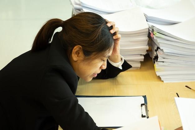Onderneemster rustende handen op hoofd met ogen dicht bij het werkbureau in bureau.