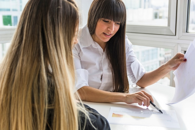 Onderneemster twee die het bedrijfsrapport in het bureau analyseert